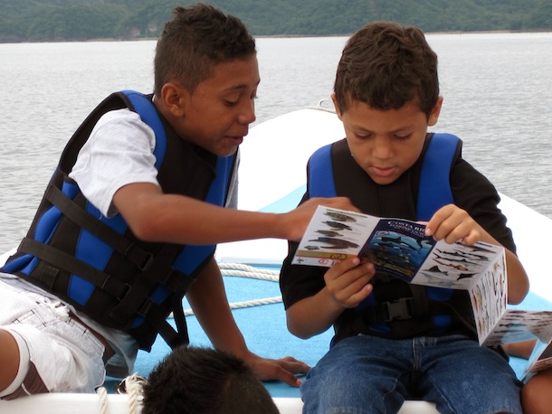 2 boys in a boat intently looking at a field guide
