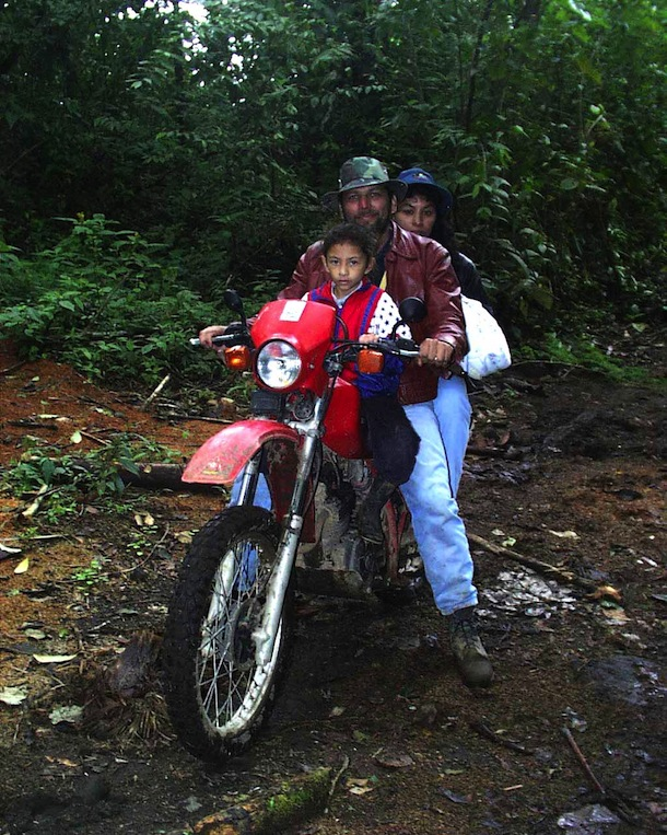 Landowner Oscar, wife and child traveling on red motorcycle
