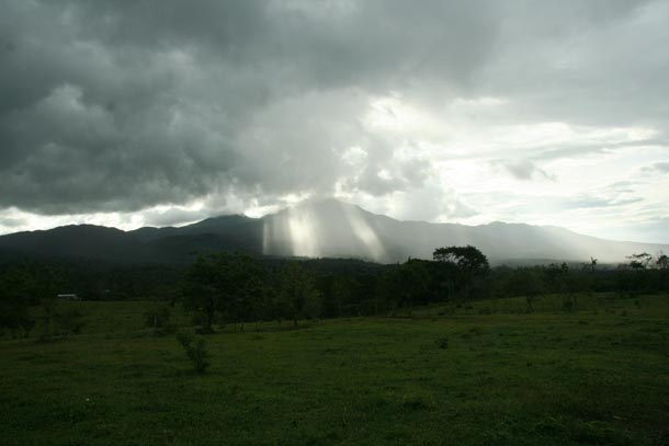 Volcan Cacao seen from the east with forest wrapping all around it, under heavy rain clouds