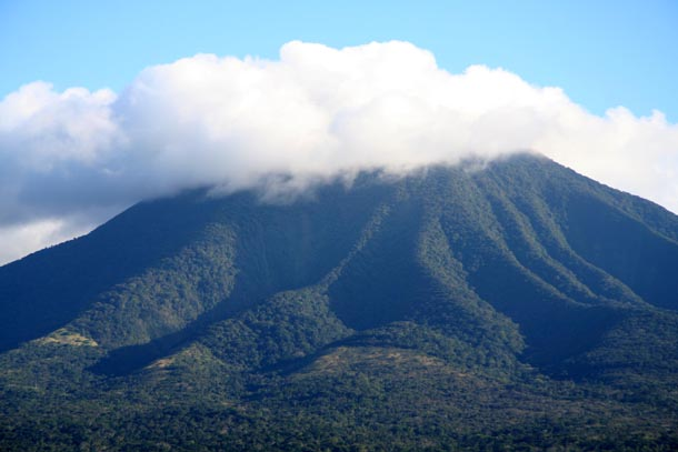 A single forested volcano, Volcan Orosi, with steep rugged slopes, topped with a white cloud that is large and dark gray to the left (east) and thin and fluffy white to the right (west)