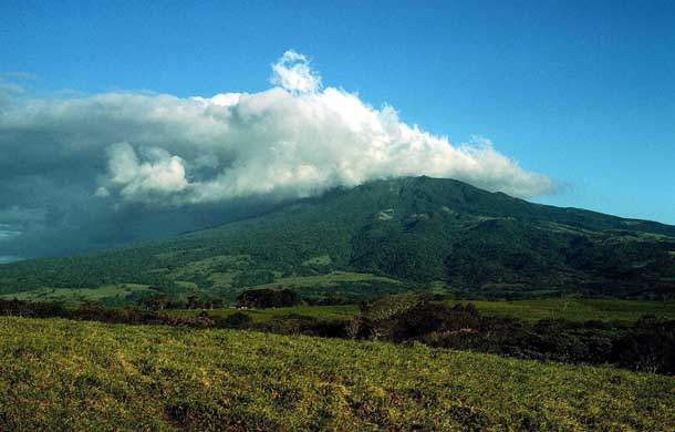 A sprawling forested volcano, Rincon, from afar topped with clouds in a blue sky. On the left (east side) the clouds are thick and dark, on the right they vanish into wisps in a blue sky