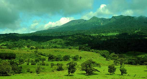 View of Caribbean side of Volcan Rincon massif, covered in forest, seen from lowland pasture