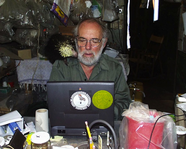 Dan Janzen at work with pet porcupine Espinita exploring his cheek, and 1999 vintage laptop