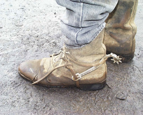 Closeup of landowner's boots and spurs during roadside land negotiation