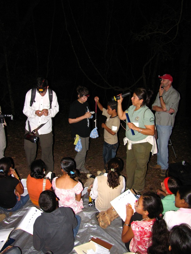 At night, with flashlights and headlamps, school children and teacher out with bat researcher weighing bat in cloth bag.